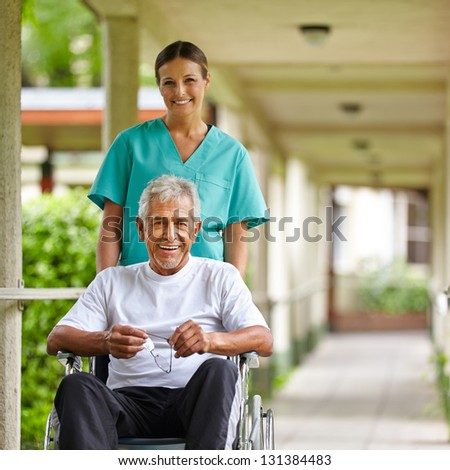 Senior man in wheelchair with nurse on a stroll through the hospital garden - stock photo