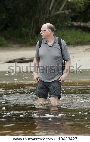 senior man is crossing a river with his backpack - stock photo