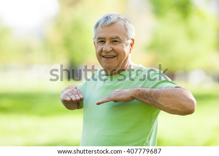 Senior man is exercising in park. Active retirement. - stock photo