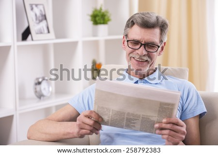 Senior man is reading newspaper at home. - stock photo