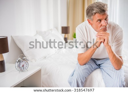 Senior man is sitting in bed and looking away. - stock photo