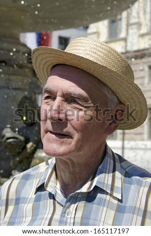 Senior man is standing by the fountain. - stock photo