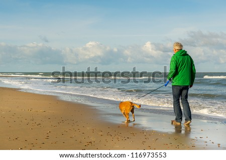 Senior man is walking the dog at the beach - stock photo