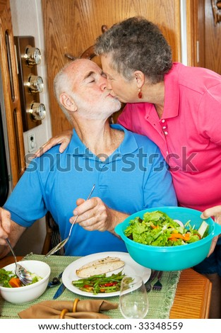 Senior man kisses his wife as she serves him dinner in their motor home. - stock photo