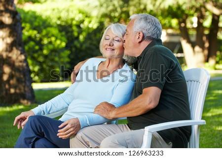Senior man kissing his woman in a summer garden - stock photo