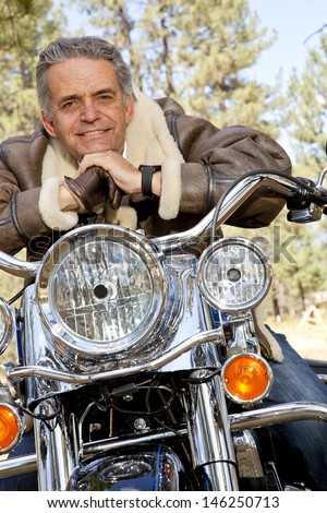 Senior man leaning on motorcycle handlebars - stock photo