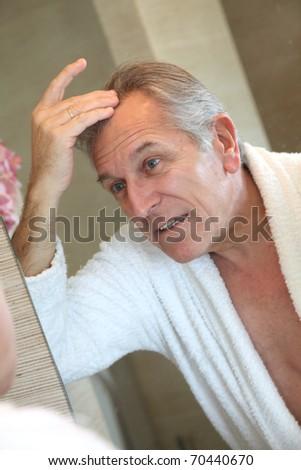 Senior man looking at hair in mirror - stock photo