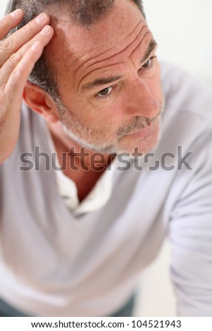 Senior man looking at his hair in mirror - stock photo