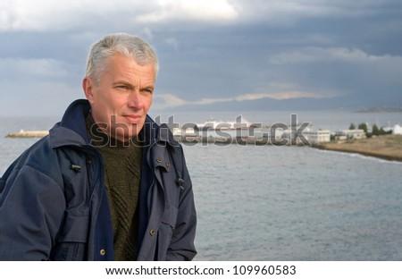 Senior man looking away against the sea - stock photo