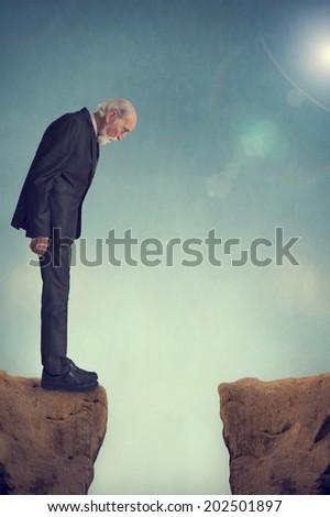 senior man looking down a mountain crevasse - stock photo