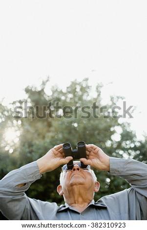Senior man looking through binoculars - stock photo