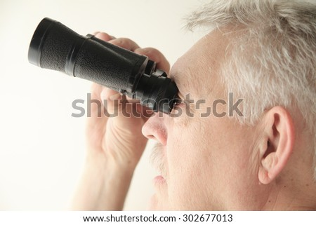 Senior man looking upward with an old pair of binoculars, copy space included. - stock photo