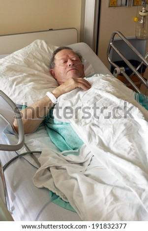 Senior man lying in hospital bed getting oxygen in intensive care unit, vertical - stock photo