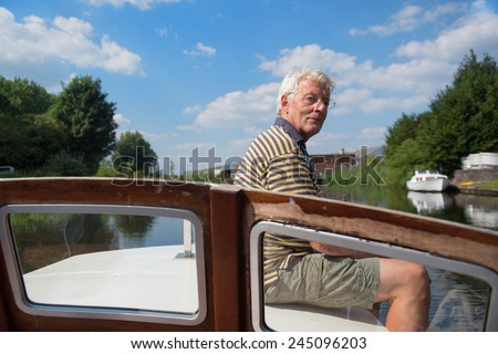 Senior man making day trip on boat at river - stock photo
