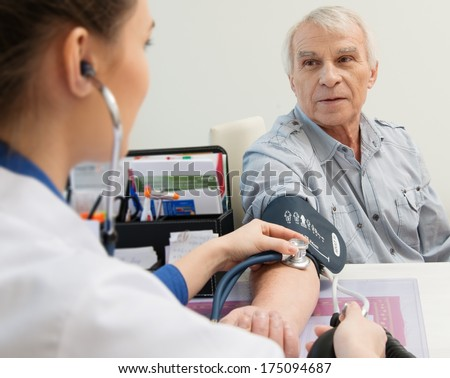 Senior man measuring blood pressure at doctor's office   - stock photo