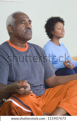 Senior man meditating in lotus position - stock photo