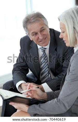 Senior man meeting senior businesswoman - stock photo