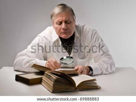 Senior man observing a book with a magnifying glass - stock photo