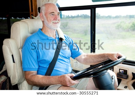 Senior man on vacation driving his motor home. - stock photo