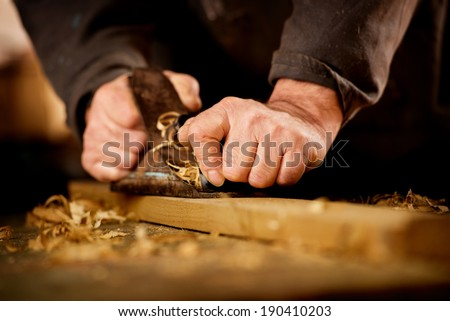 Senior man or carpenter doing woodworking planing the surface of a plank of wood in his workshop with a manual plane as he enjoys his creative hobby - stock photo
