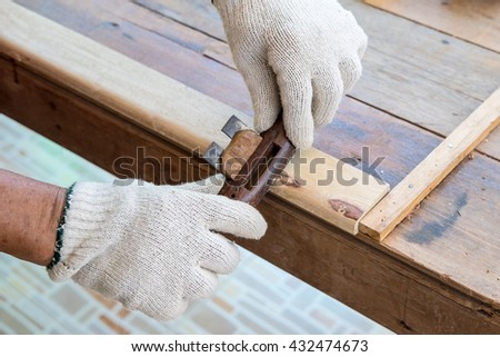 Senior man or carpenter doing woodworking planing the surface of a plank of wood in his workshop - stock photo