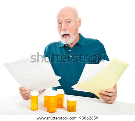 Senior man overwhelmed by the cost of his medical care and prescription drugs.  White background. - stock photo