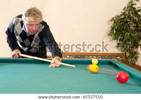 Senior man playing a game of carambole billiards - selective focus on the billiard balls - stock photo