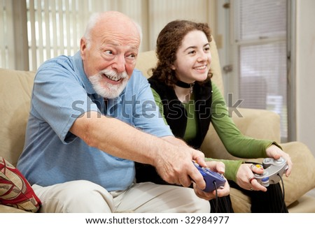 Senior man playing a video game with his teenage granddaughter. - stock photo