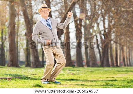Senior man playing air guitar in the park - stock photo