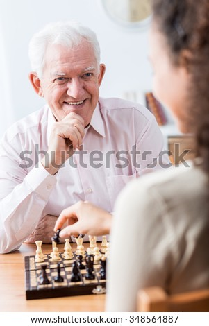 Senior man playing chess with his carer - stock photo