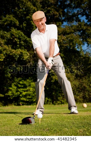 Senior man playing golf attempting the first stroke in the teeing area (focus is on the ball!) - stock photo