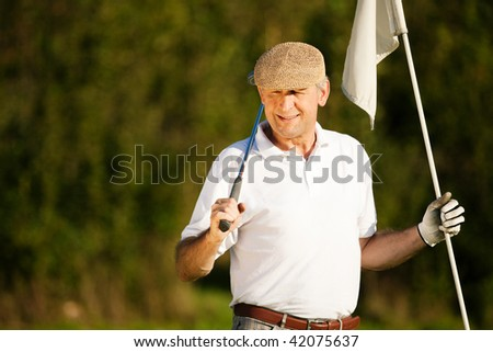 Senior man playing golf holding the flag in his hand - stock photo