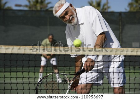 Senior man playing tennis - stock photo