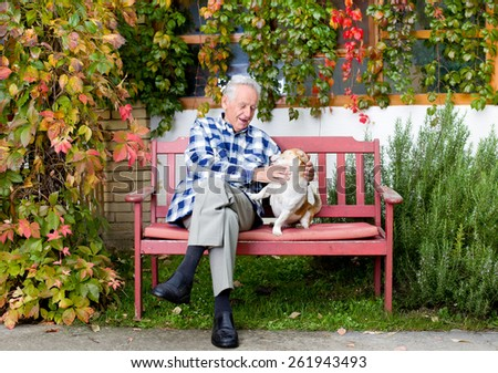 Senior man playing with his dog on the bench in courtyard - stock photo