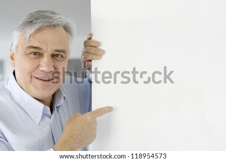 Senior man pointing at message board - stock photo