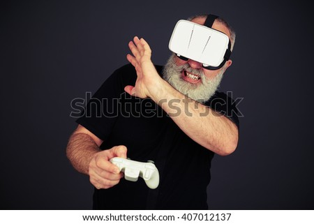 Senior man protect his face playing on the joystick using virtual reality glasses, on black background - stock photo