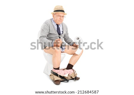 Senior man pushing hard seated on a toilet isolated on white background - stock photo
