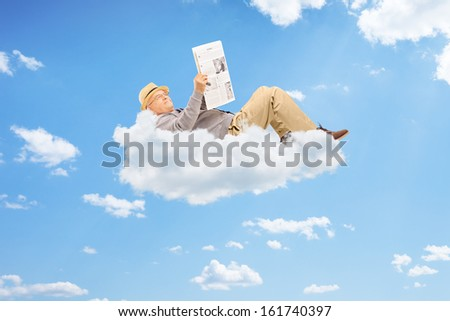 Senior man reading a newspaper and lying on clouds - stock photo