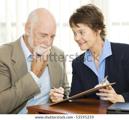 Senior man reading and thinking about a contract while eager businesswoman encourages him to sign. - stock photo
