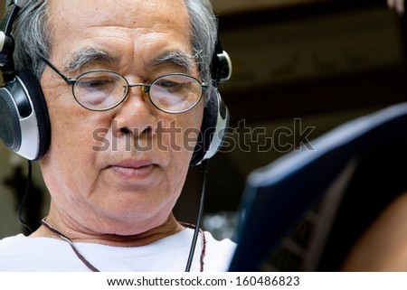 Senior man relaxing at home reading E-book on his tablet. - stock photo