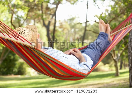 Senior Man Relaxing In Hammock - stock photo
