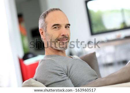 Senior man relaxing in sofa at home - stock photo