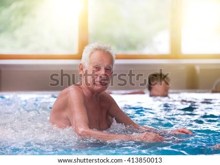 Senior man resting in jacuzzi in spa resort - stock photo