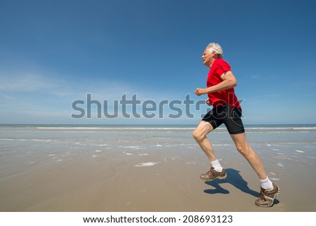 Senior man running at the beach - stock photo