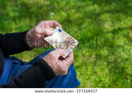 Senior man's hands holding Euro banknote. Struggling pensioners concept. - stock photo