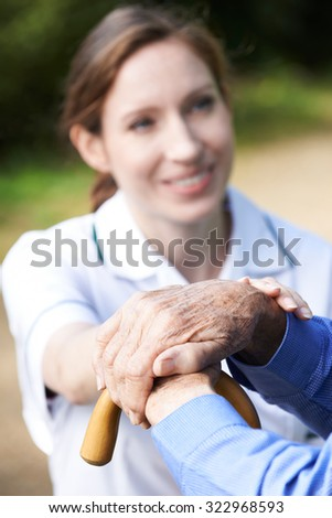 Senior Man's Hands Resting On Walking Stick With Care Worker In Background - stock photo