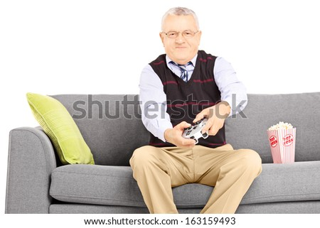 Senior man seated on a sofa playing video games isolated on white background - stock photo