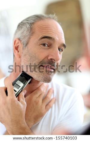 Senior man shaving beard with electric razor - stock photo