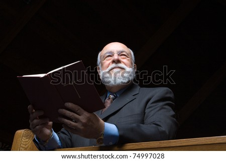 Senior man shot from below holding a hymnal in church pew. - stock photo