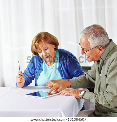 Senior man showing old woman in nursing home a tablet computer - stock photo